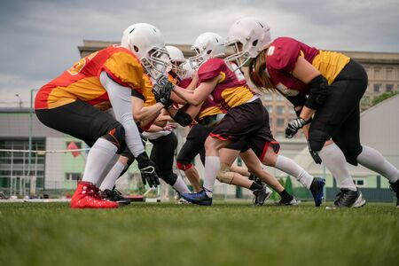 Photo of female team in helmets playing rugby on playground