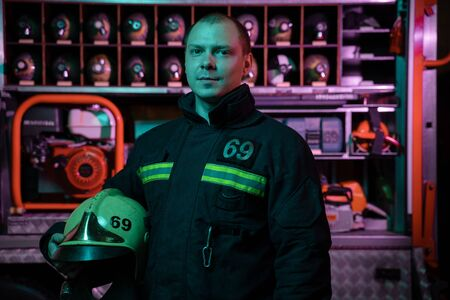 Portrait of serious fireman looking to camera with helmet in hand in fire uniform near fire truck Stockfoto
