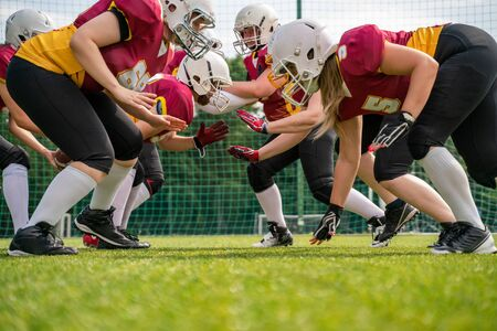 Photo of athletes women wearing helmets playing american football on sports field