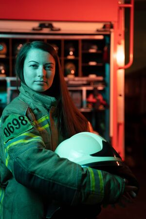 Photo of girl firefighter with long hair with helmet in her hands at fire station. Stockfoto