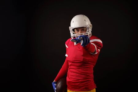 Photo of american female football player in helmet with arm outstretched forward