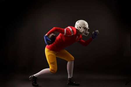 Side view of running woman in white helmet with rugby ball in her hand in studio