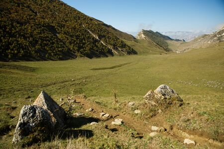 Photo of mountain area with blue clear sky, stones, green field on summer 스톡 콘텐츠 - 132109793