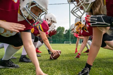 Photo of athletes women wearing white helmets playing american football on sports field