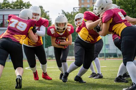 Full-length image of athletes women playing american football on green lawn