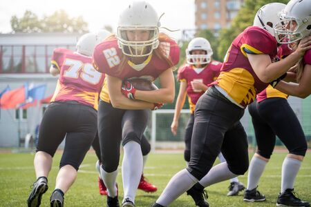 Full-length image of athletes women playing american football on green lawn on summer day Standard-Bild