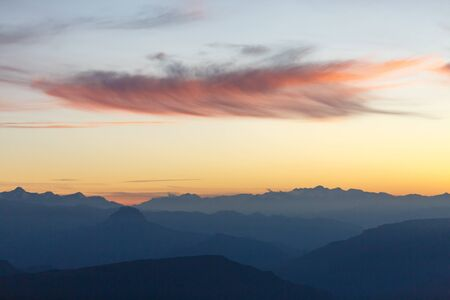 Picture of evening foggy mountain terrain with red sky Banco de Imagens