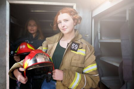 Image of two female firefighters in fire truck