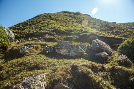 Image of mountain area with blue clear sky, stones, green field on summer 스톡 콘텐츠 - 132110049