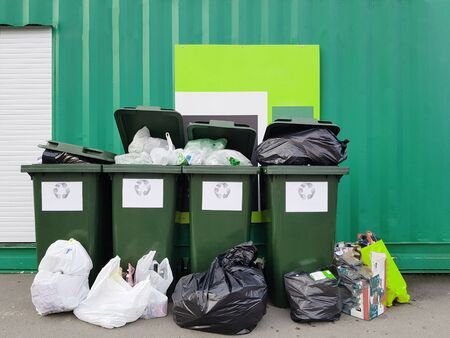 Photo of garbage cans, garbage bags near green fence.