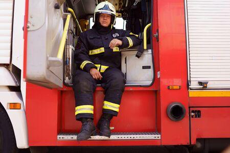 Photo of fireman wearing helmet sitting in fire truck at fire station