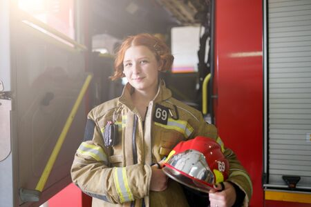 Photo of ginger woman firefighter with helmet in hands against backdrop of fire truck
