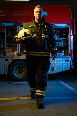 Full-length photo of young firefighter with helmet in his hand looking into camera while standing near fire truck