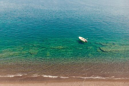 Image of sandy shore, sailing boat, azure sea.