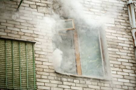 Photo of brick house with smoke coming out of window Stock Photo