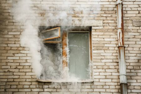 Picture of brick house with smoke coming out of window. Stock Photo