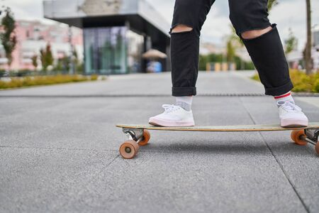 Image of legs of woman in black jeans riding skateboard on street in city