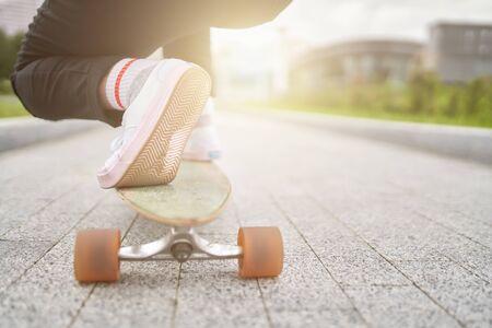 Bild von Frauenbeinen in weißen Turnschuhen, die am Sommertag auf der Straße in der Stadt Skateboard fahren. Lensflare-Effekt Standard-Bild