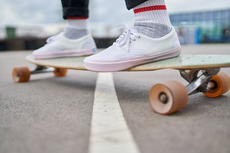 Photo of woman's legs in white sneakers riding skateboard on street in city on summer day Stock Photo