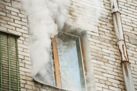 Image of brick house with smoke coming out of window Stock Photo