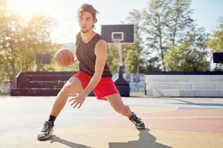 Photo of athlete in blue T-shirt playing basketball on playground
