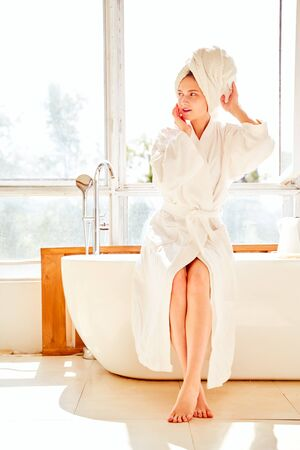 Photo of young girl in white bathrobe and with towel on her head standing near bath in room with large window.
