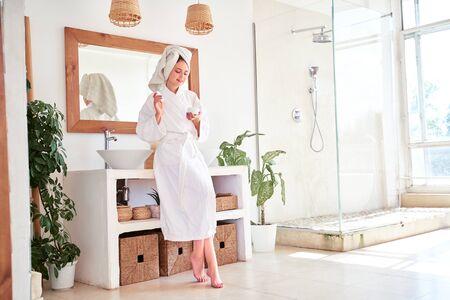 Foto de cuerpo entero de mujer en bata de baño con crema en sus manos en el baño.