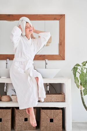 Full-length image of happy woman in white bathrobe and with towel on her head sitting on sink