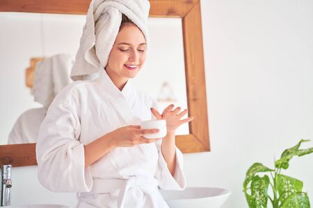 Photo of woman in bathrobe with cream in her hands in bathroom . 스톡 콘텐츠