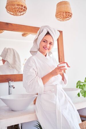 Photo of young woman in bathrobe with cream in her hands in bathroom. 스톡 콘텐츠