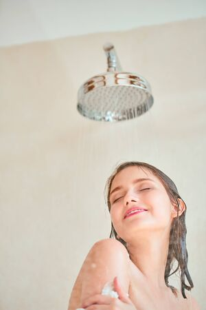 Photo of young woman taking shower .