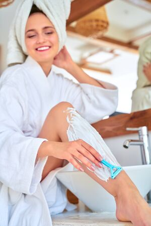 Photo of happy woman in white coat shaving her legs in bath