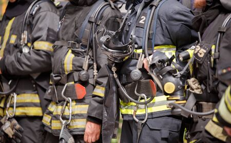 Several standing firefighters in special suits and gas masks