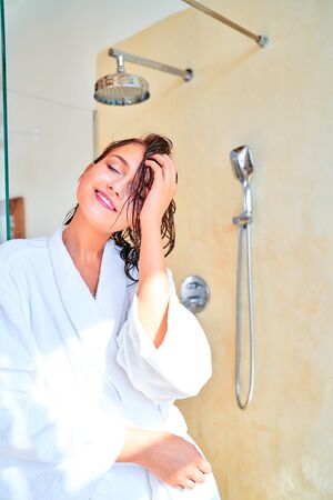 Picture of happy brunette woman with wet hair in white bathrobe while standing in bath 스톡 콘텐츠