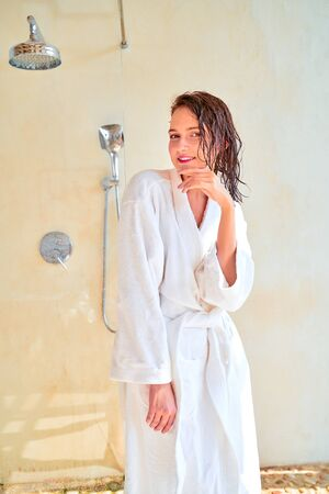 Photo of happy brunette with wet hair in white bathrobe standing in bath