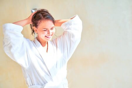 Photo of smiling brunette girl with wet hair in white bathrobe standing in bath.