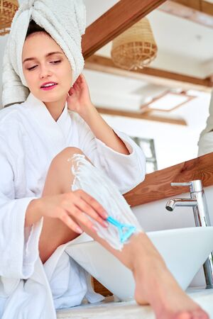 Image of woman in white coat shaving her legs in bath 스톡 콘텐츠