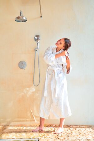 Full-length photo of young brunette with wet hair in white bathrobe standing in bath