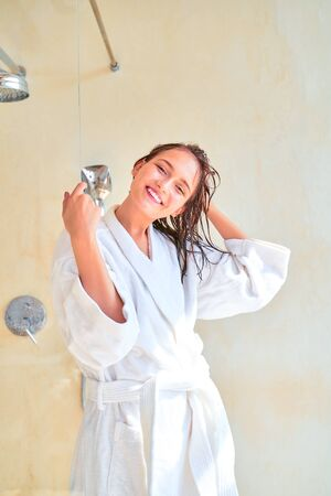 Photo of happy brunette woman with wet hair in white bathrobe standing in bath.