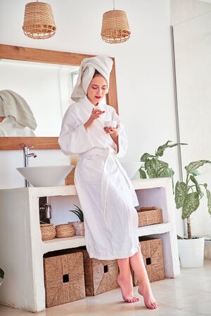 Full-length photo of happy woman in bathrobe with cream in her hands in bathroom.