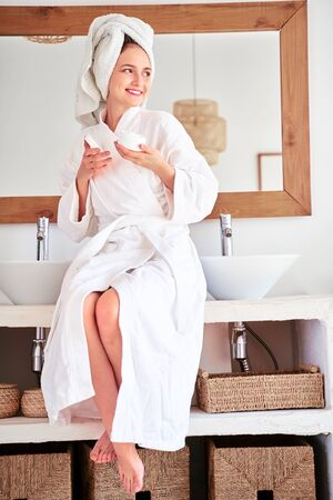 Full-length photo of smiling woman in bathrobe with cream in her hands in bathroom.