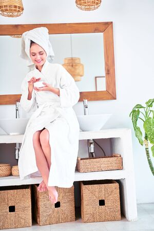 Picture of happy woman with bathrobe with cream in her hands standing in bathroom.