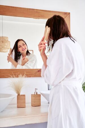 Image of brunette combing her hair in front of bathtub mirror 스톡 콘텐츠