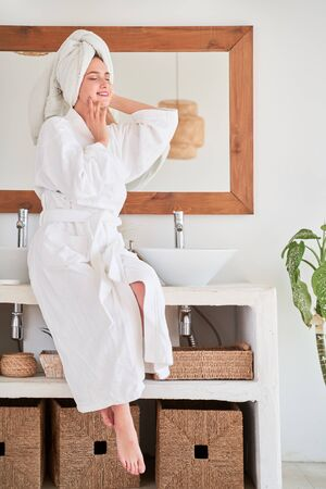 Full-length image of happy girl in white bathrobe and with towel on her head sitting on sink.