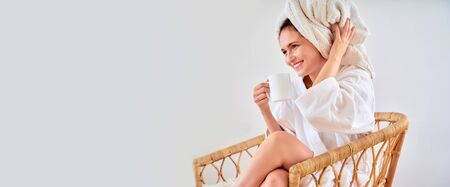 Image of woman in white bathrobe with mug in her hand sitting on wicker chair