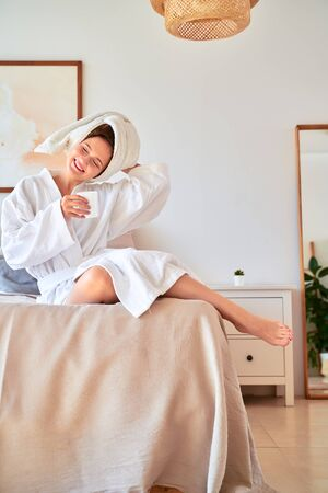 Image of smiling woman in white bathrobe with mug of coffee in her hands lying on bed.