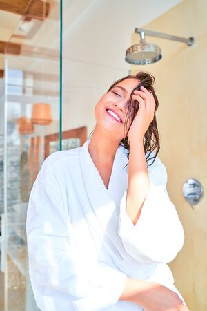 Picture of smiling brunette woman with wet hair in white bathrobe while standing in bath.