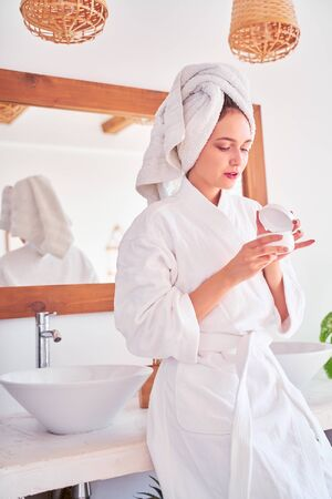 Image of young woman in bathrobe with cream in her hands in bathroom . 스톡 콘텐츠