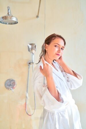 Photo of young brunette woman with wet hair in white bathrobe standing in bath.