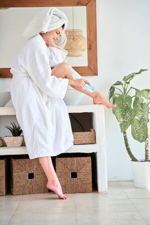 Full-length photo of woman in white coat shaving her legs in bath Stockfoto